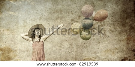 Brunette girl with colour balloons at blue sky background. Photo in old image style. - stock photo