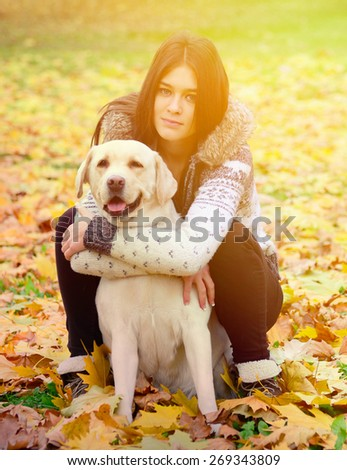 Brunette girl with dog in nature - stock photo