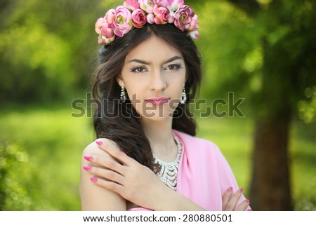 Brunette girl with flower chaplet in green filed wearing in pink dress on green field. - stock photo