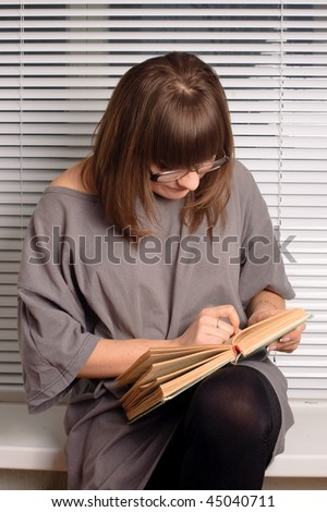 Brunette girl with glasses reading a book on the windowsill - stock photo
