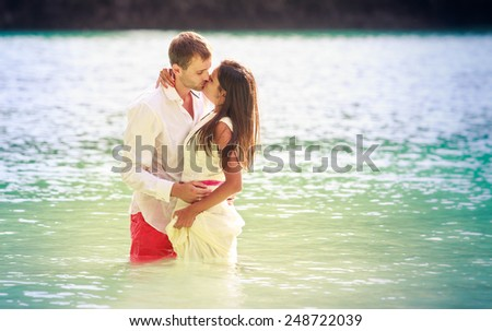 brunette girl with handsome man stand in sea water in island bay with green mountain background - stock photo