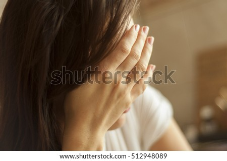 Brunette girl with headache holding hand on her head.
