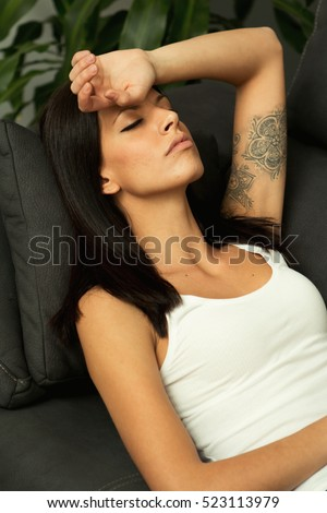 Brunette girl with headache resting on the sofa at home