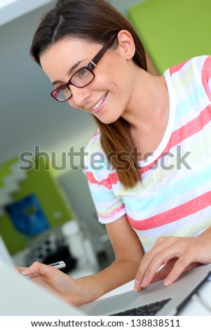 Brunette girl working on laptop computer