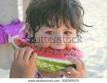 brunette girl 3 years eats a slice of watermelon outdoors - stock photo