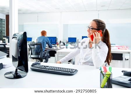 Brunette glasses businesswoman working in office talking smartphone - stock photo