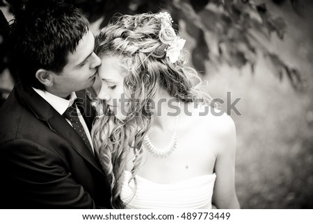 Brunette groom kisses bride's forehead tender while they stand in the park