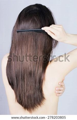 Brunette hair back shot, brushing her hair - stock photo