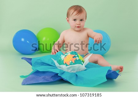 Brunette hair blue eyed baby boy holding hand up and sitting in front of his blue yellow green and orange giant fishy birthday cupcake with tissue paper on a seamless green background with balloons - stock photo