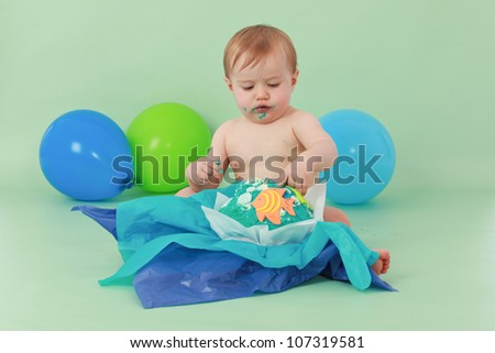 Brunette hair blue eyed baby boy looking down at his  ocean themed birthday party cupcake with orange fish and seaweed on it while sitting on green background with green and blue balloons behind him. - stock photo