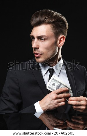brunette handsome man in a suit on a dark background with money
