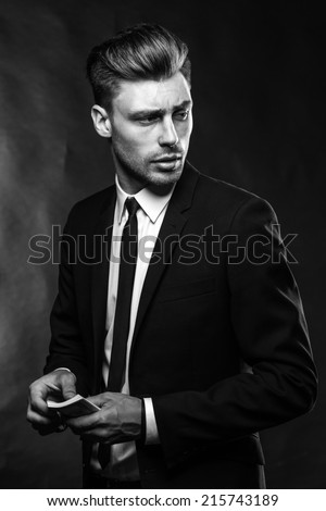 brunette handsome man in a suit on a dark background with money - stock photo