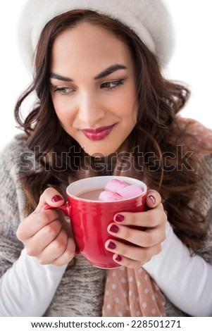 Brunette having hot chocolate with marshmallow on white background - stock photo