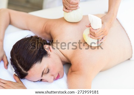 Brunette having massage with herbal compresses in the health spa - stock photo