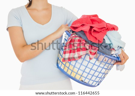 Brunette holding a basket full of laundry on white background