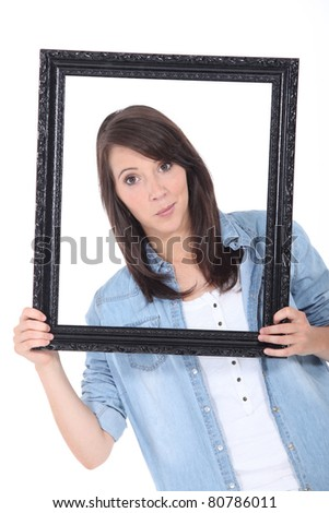 Brunette holding empty picture frame - stock photo