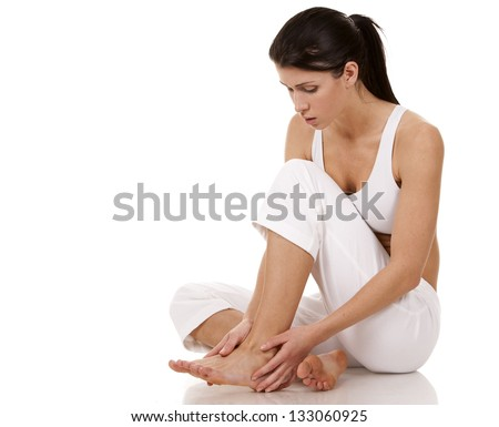 brunette holding her feet on white isolated background - stock photo