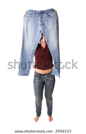 Brunette holding up her old jeans that were 5 sizes bigger then she is wearing today - stock photo