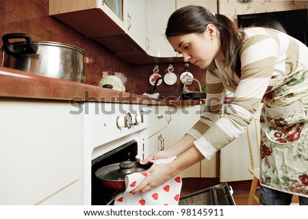 Brunette housewife taking hot frying pan out from oven