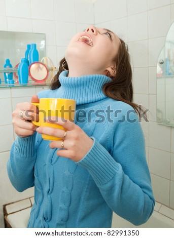 Brunette illness girl gargles her throat in bath - stock photo