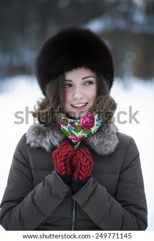 Brunette in a fur hat with a sweet wide smile - stock photo