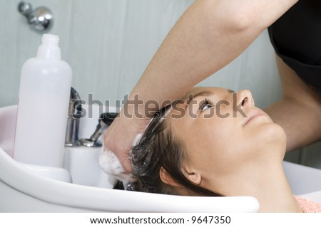 brunette in a salon getting washed her hair with shampoo - stock photo