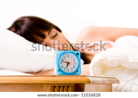 brunette in bed with an alarmclock at the front. Foucus is at the alarmclock since this is the main subject of this image. - stock photo