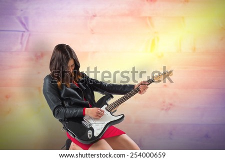 Brunette in biker jacket playing guitar against yellow and purple planks - stock photo