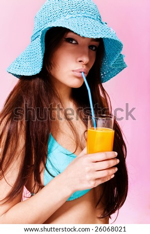 brunette in bikini and hat drinking juice - stock photo