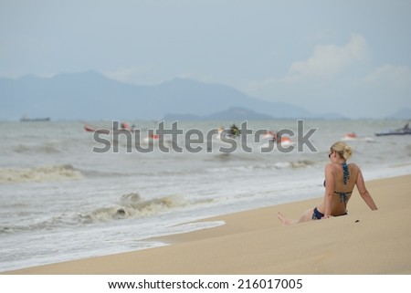 brunette in bikini sitting on the beach  - stock photo
