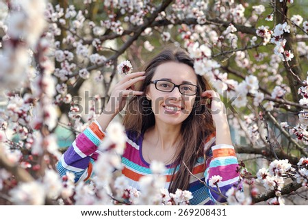 Brunette in glasses on a background of a blossoming tree in spring. - stock photo