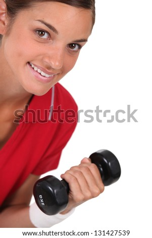 Brunette in gym with dumbbell - stock photo
