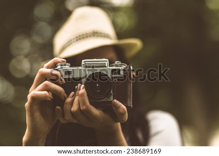 Brunette in straw hat taking picture in the park - stock photo
