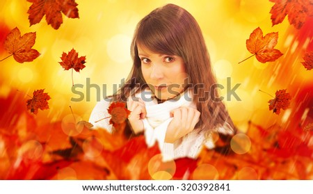 Brunette in winter clothes smiling at camera against orange abstract light spot design