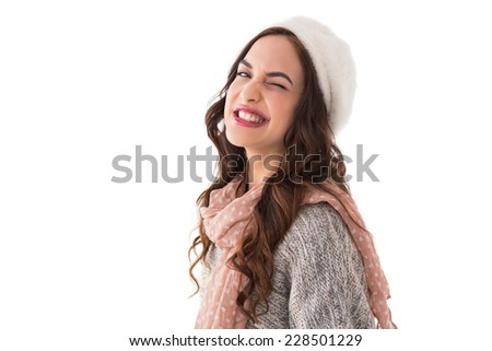 Brunette in winter clothes winking her eye on white background - stock photo