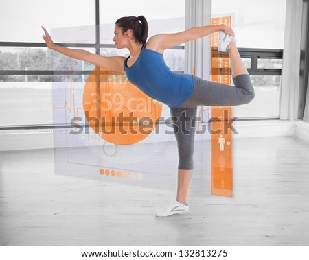 Brunette in yoga pose with futuristic interface next to her showing lost calories - stock photo
