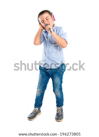 Brunette kid listening and singing music over white background