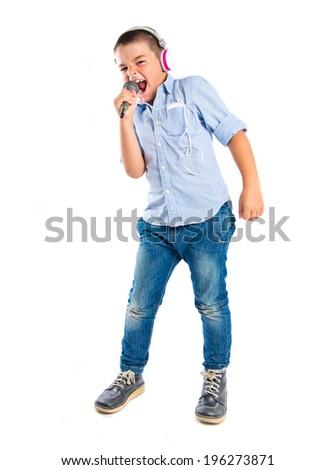 Brunette kid listening and singing music over white background  - stock photo