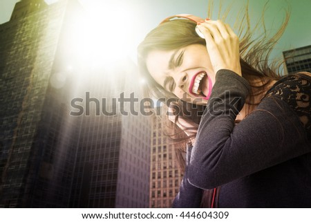 Brunette latina girl listening to music in the city - stock photo