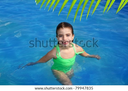 brunette little girl in swimming pool smiling with missing front teeth [Photo Illustration] - stock photo