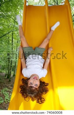 Brunette little girl upside down playground slide forest tree park [Photo Illustration] - stock photo