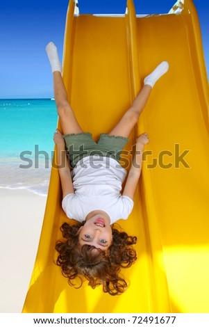 Brunette little girl upside down playground slide in Caribbean beach [Photo Illustration] - stock photo