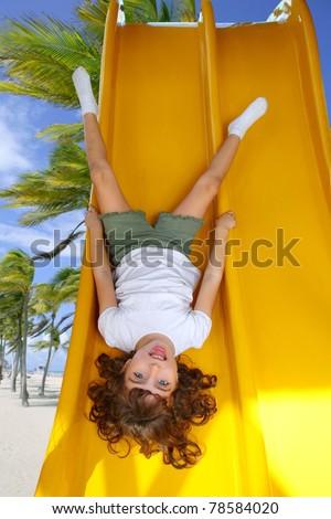 Brunette little girl upside down playground slide tropical palm trees beach [Photo Illustration] - stock photo