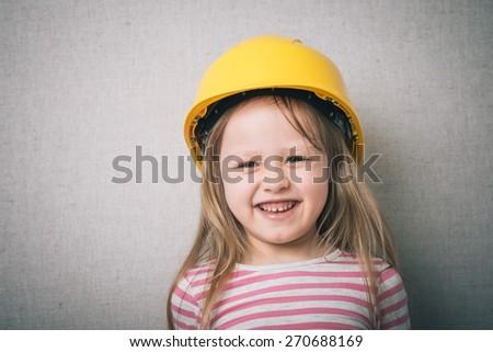 Brunette little girl with a yellow helmet  - stock photo