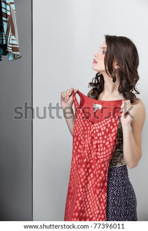 brunette looking at a red dress in the mirror - stock photo