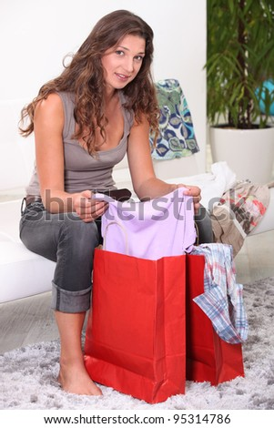 Brunette looking through bags of shopping - stock photo