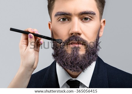 Brunette man with violet beard and eyebrows, wearing in dark blue suit and tie, looking at camera. Woman's hand with make-up brush near his face, on white background, in studio, close up - stock photo