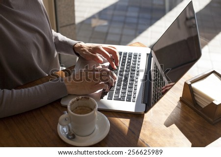 brunette mauve sweater woman typing keyboard pc laptop with white small cup cappuccino coffee on light brown wooden table cafe - stock photo