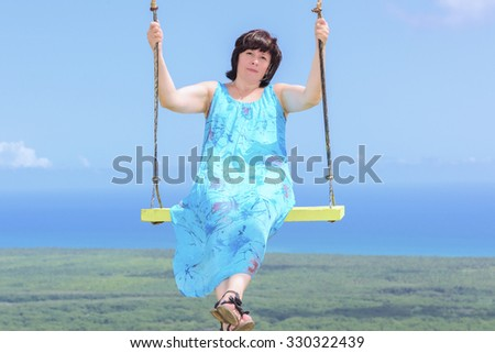 Brunette middle aged woman riding on a swing suspended high - stock photo