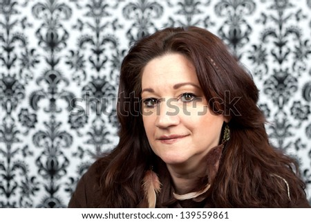 Brunette middle aged woman with feather hair extensions and accessories.